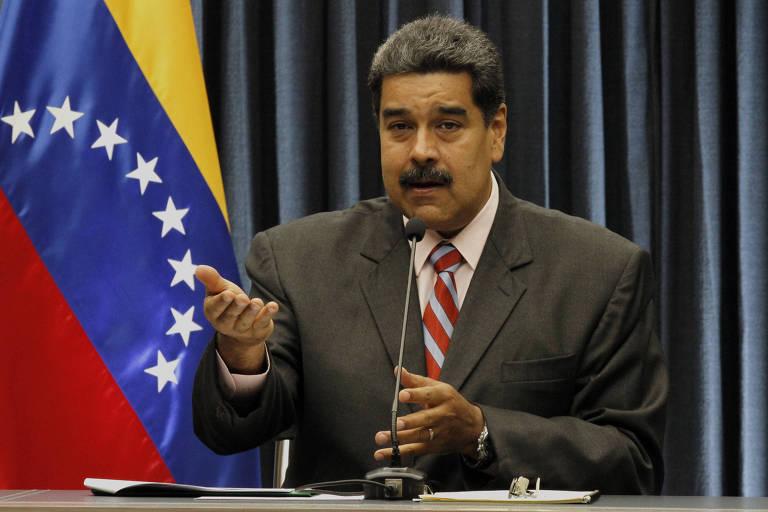 Maduro aparece sentado, de terno cinza, camisa branca e gravata listrada em azul claro e vermelho, falando ao microfone. A seu lado esquerdo está uma bandeira da Venezuela. O local onde ele fala tem como fundo uma cortina de cor preta.