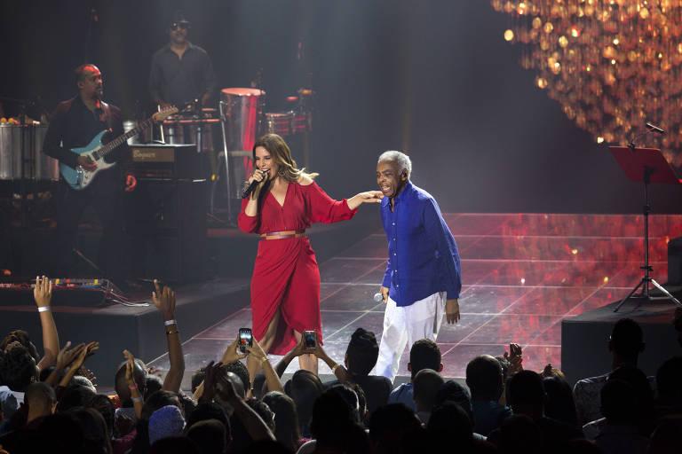 Ivete Sangalo e Gilberto Gil em show conjunto; muito sorridentes, ela, usando um vestido vermelho, coloca a mão no ombro do cantor, que veste camisa azul-royal e calça branca