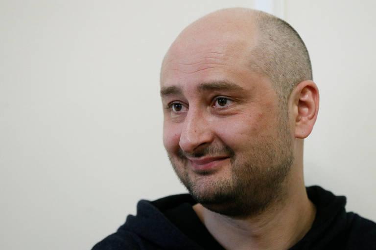 De casaco preto, Babtchenko sorri ao conversar com jornalistas. Ele aparece apenas do pescoço para cima à frente de uma parede branca.