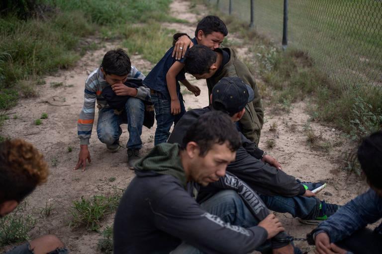 Quatro meninos se abraçam ao fundo, chorando. À frente deles um homem está com a cabeça baixa em frente a outro homem, que não aparece na imagem. Os seis estão em uma área de terra batida com mato perto de uma cerca, cuja parte de baixo é vista na foto.