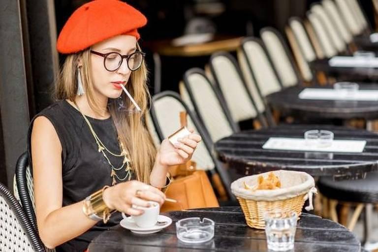Mulher, com uma boina vermelha, está sentada em um café fumando