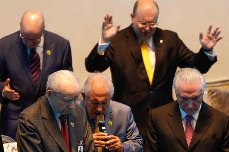 Com pessoas orando ao redor, o presidente da república, Michel Temer participa da Convenção Nacional das Assembleias de Deus