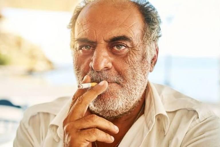 Homem com feições gregas traga um cigarro
