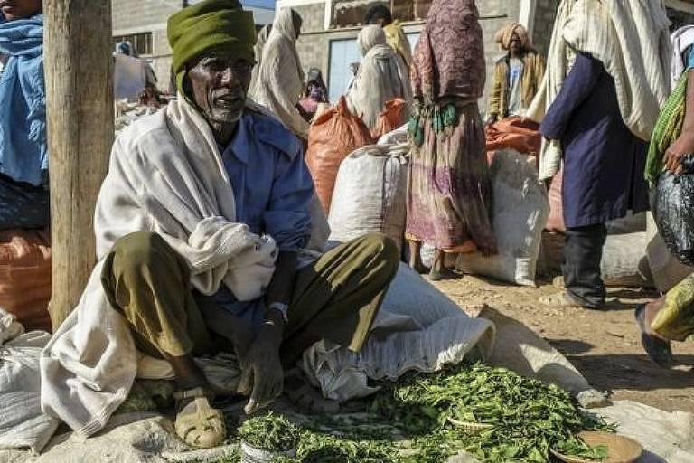 Homem sentado na rua. Em sua frente, folhas de khat espalhadas pelo chão