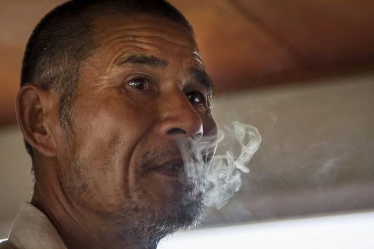 Homem solta fumaça de cigarro pelo nariz