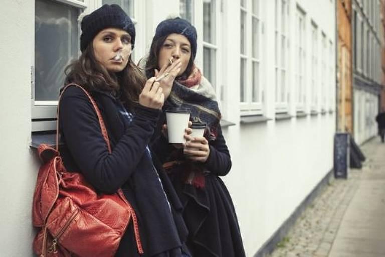 Duas mulheres com roupas de frio fumam na rua. Ambas seguram copos de bebidas quentes