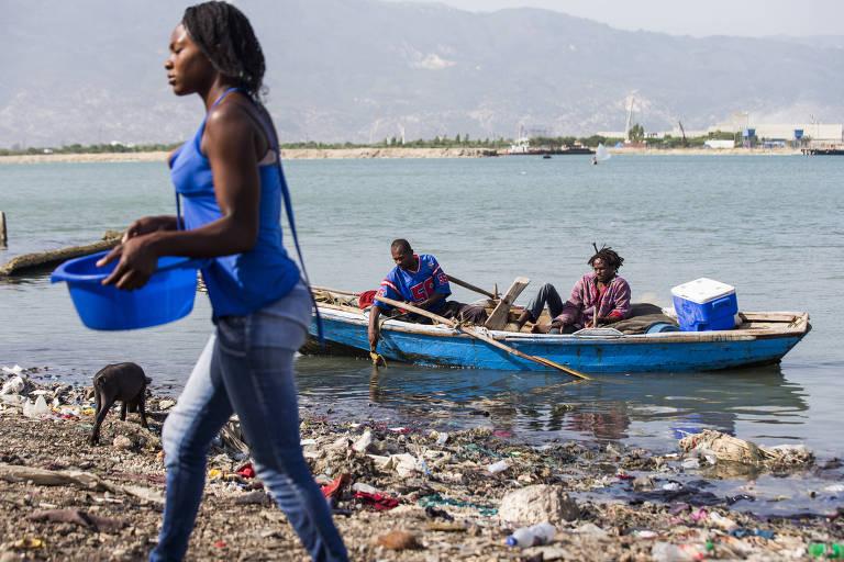 Pessoas caminham e navegam ao lado de lixo acumulado às margens de rio