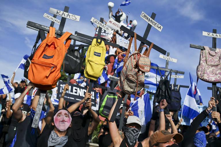 Grupo de dez manifestantes carregam cruzes pretas de madeira, cada uma delas com uma mochila pendurada e dois cartazes, com o nome da vítima e a cidade de onde ela veio. Entre eles há pessoas com bandeiras da Nicarágua e roupas com as cores do país.