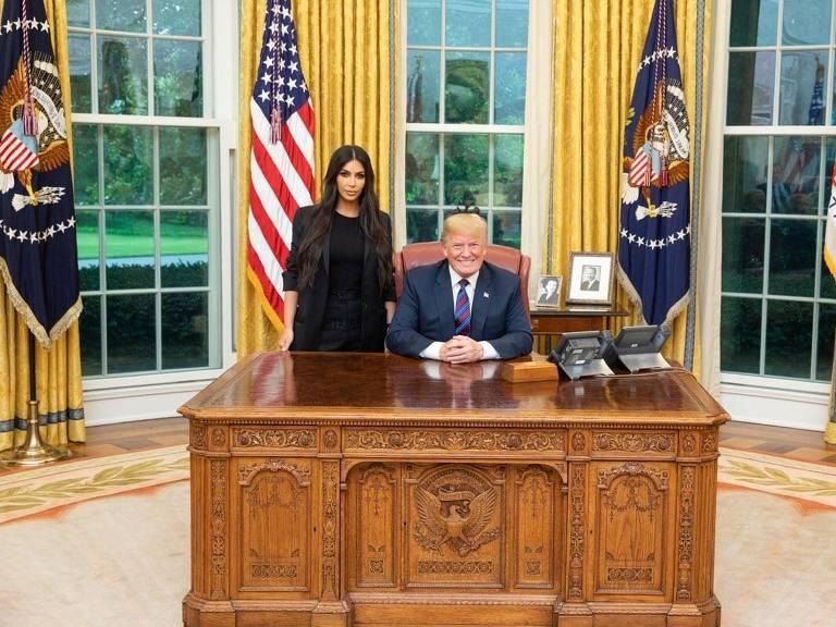 kim kardashian em pé ao lado de trump sentado em sua mesa