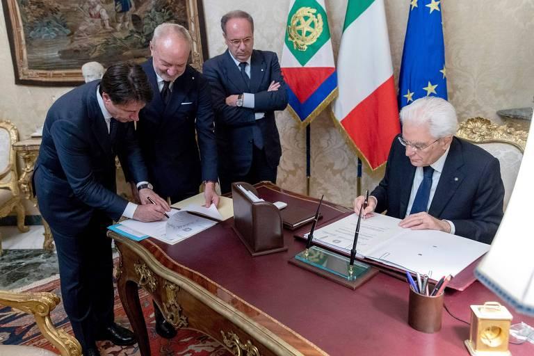 O recém-nomeado premiê Giuseppe Conte (à esq.) e o presidente da Itália, Sergio Mattarella (à dir.), assinam a lista do novo gabinete no Palácio do Quirinale, em Roma