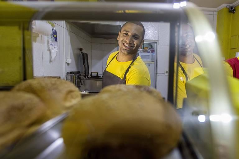 Homem atrás de estufa com pães