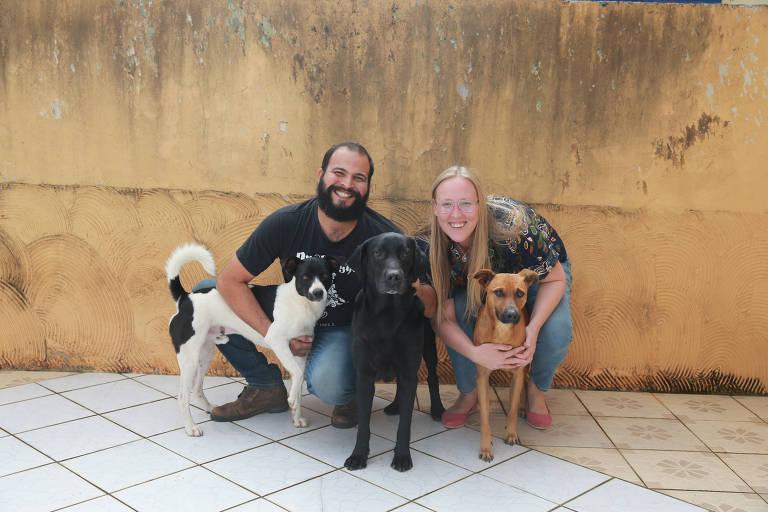 Paulo Emilio e Larissa posam para a foto com os três cachorros