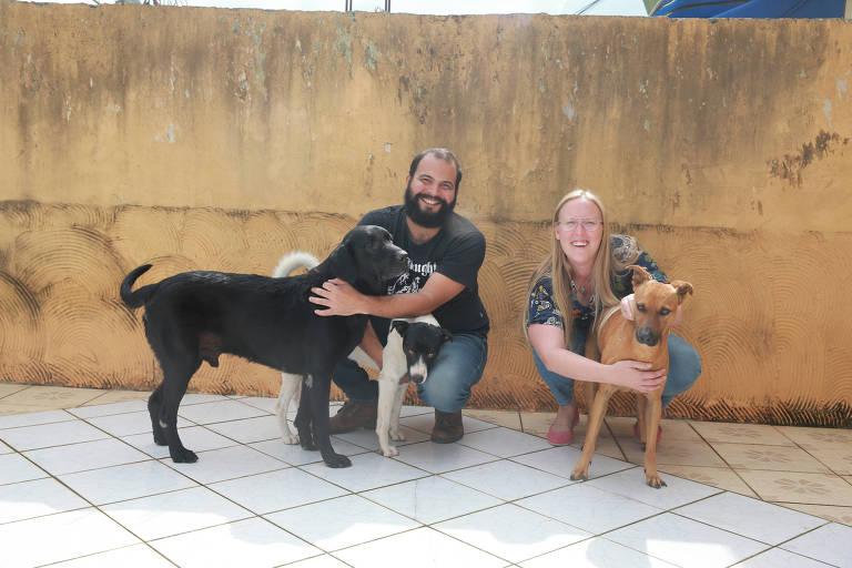 Paulo Emilio e Larissa brincam com os três cachorros