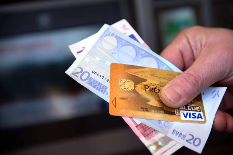 mão segura notas de euro e cartão visa