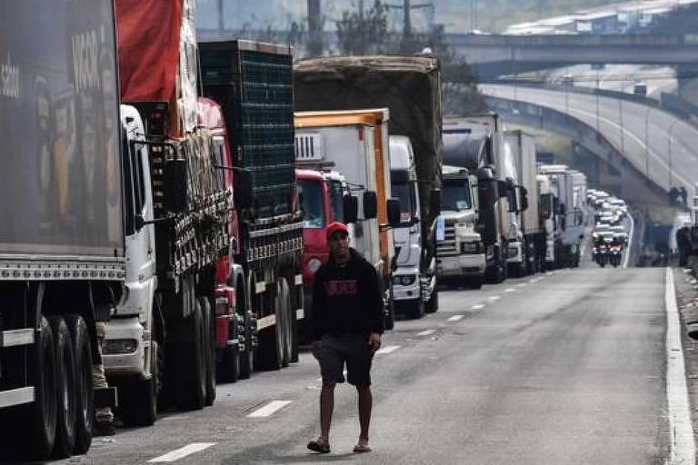 caminhões parados em fila única bloqueiam uma pista de rodovia