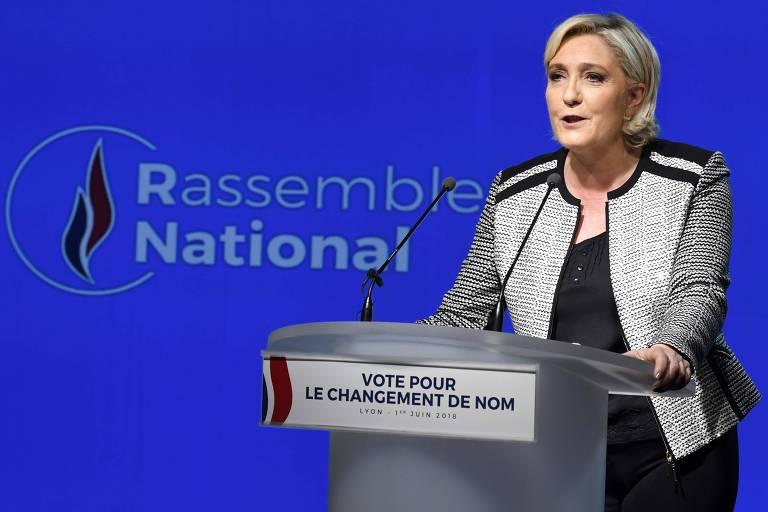um mulher loira de cabelo na altura do pescoço vestindo casado cinza e preto fala em palanque e, ao fundo, telão azul onde se lê rassemblement national