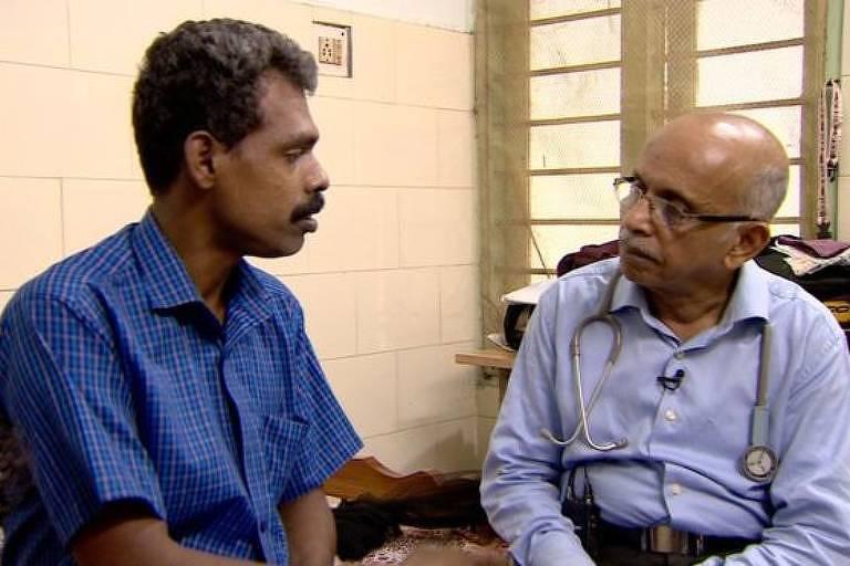 O médico indiano MR Rajagopal conversa, sentado, com paciente