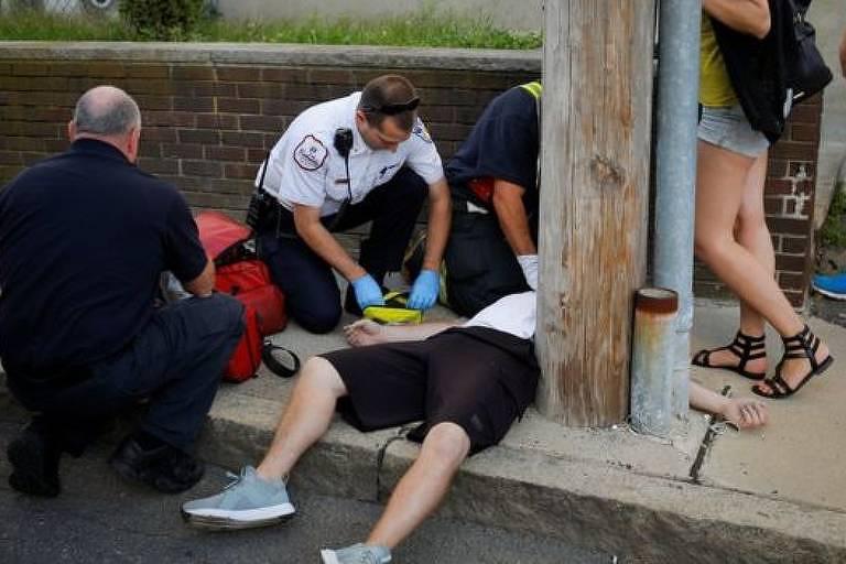 Equipe médica atende homem estendido no chão