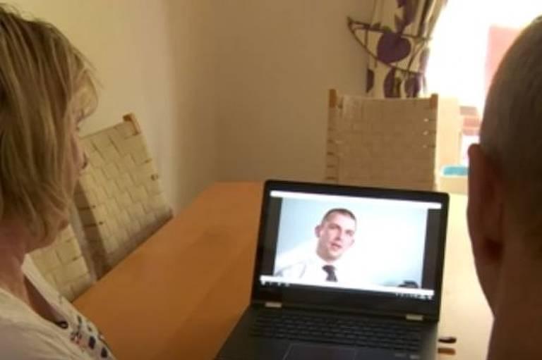 Homem e mulher olham para tela do computador, que está passando o entrevista com o especialista