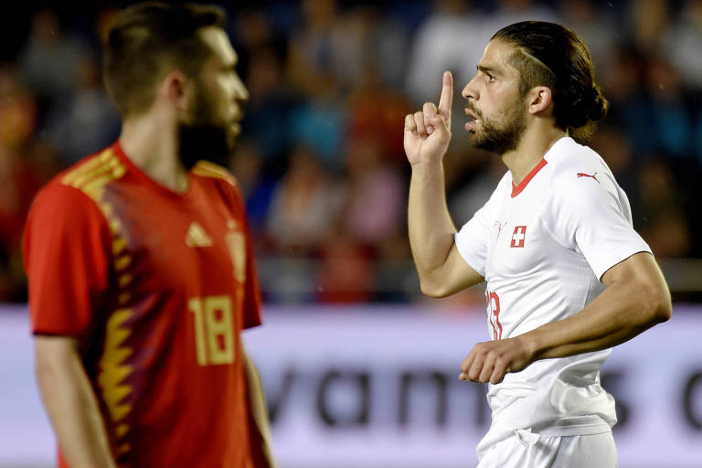 Em disputa contra Espanha em amistoso pré-Copa do Mundo, Ricardo Rodriguez comemora gol de empate no estádio La Cerámica, do Villarreal, apontando para cima. Equanto isso, jogador do time adversário lamenta