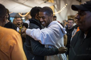 Kid Cudi, center, greets Chris Rock at Kanye West's album listening party in Moran, Wyo.