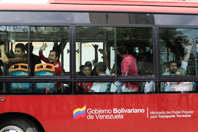 """Dentro de um ônibus vermelho com as expressões """"Governo Bolivariano da Venezuela"""" e """"Ministério do Poder Popular para o Transporte Terrestre"""", um grupo de pessoas sentadas em bancos perto da janela acena para fora do veículo."""