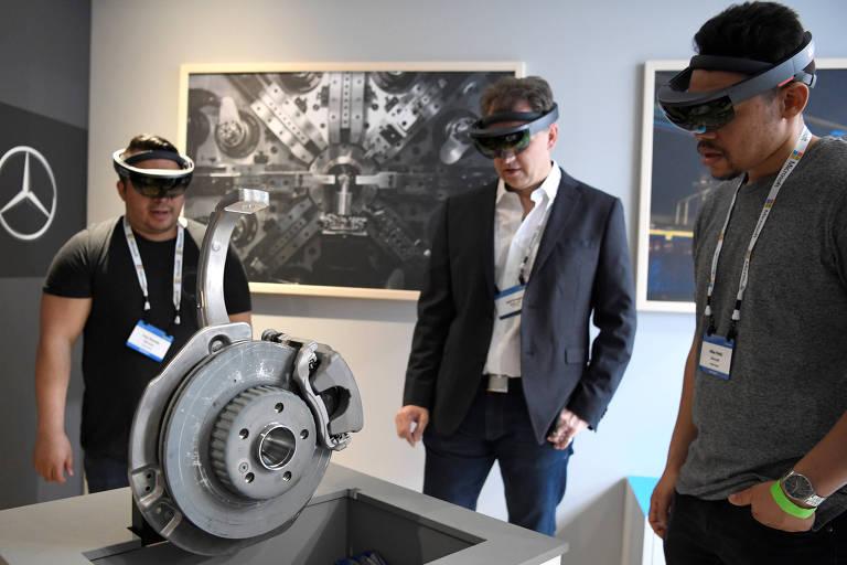 Três homens usando óculos de realidade aumentada olham para uma peça de carro