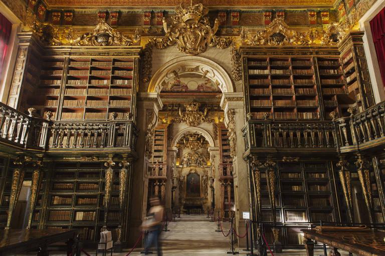 Estantes de livros de uma biblioteca antiga. O teto tem bordas douradas e um dos corredores forma um arco com pé direito alto.