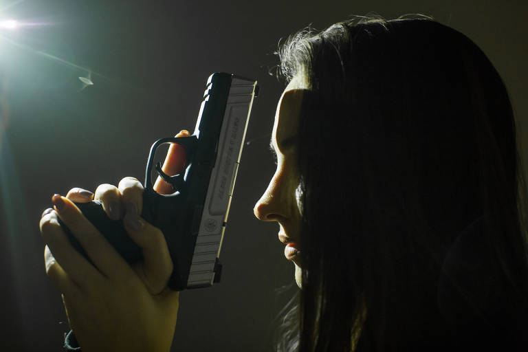 Maria Eduarda aparece de perfil, segurando a arma com as duas mãos, a contraluz.