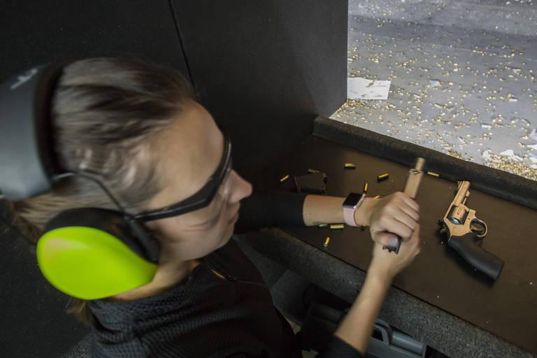 Com protetor de ouvido que cobre toda a orelha e óculos de proteção, Maria Eduarda carrega uma arma para atirar, enquanto há outra ao lado. Ao fundo vê-se o chão com restos de balas caídos.