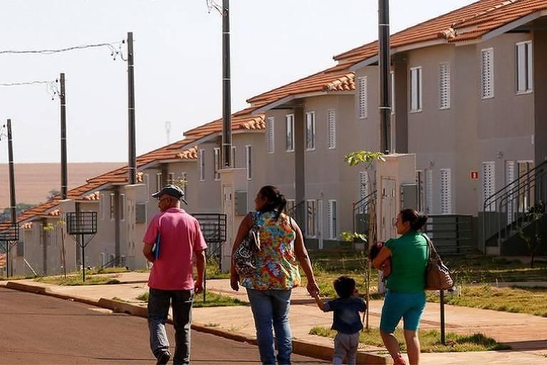 Família anda em frente de um conjunto habitacional