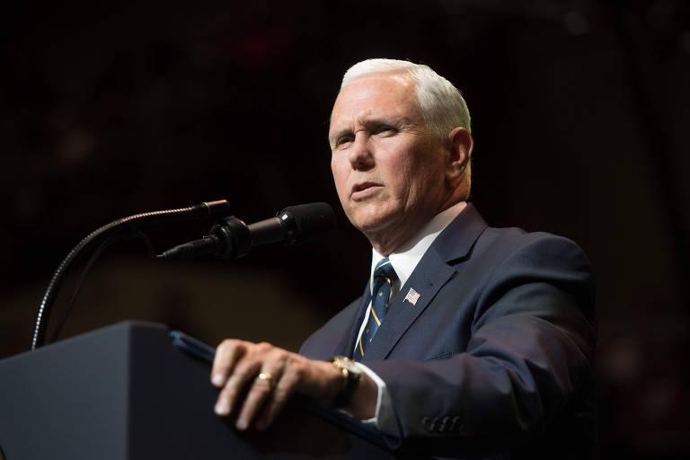 De terno preto, camisa branca e gravata preta, com a bandeira dos EUA na lapela do paletó, Mike Pence fala de pé em um púlpito preto com dois microfones. Ele aparece da cintura para cima em um local com fundo preto.