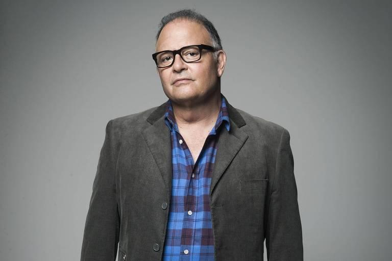 Cantor Guilherme Arantes posa com blusa cinza e camisa azul