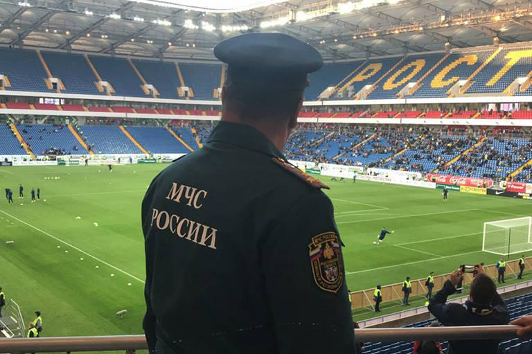 Policial com uniforme russo, de costas, olha campo de futebol