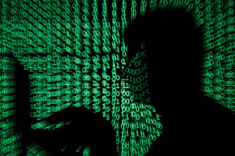 FILE PHOTO: A man holds a laptop computer as cyber code is projected on him in this illustration picture taken on May 13, 2017. REUTERS/Kacper Pempel/Illustration/File Photo ORG XMIT: AWH601