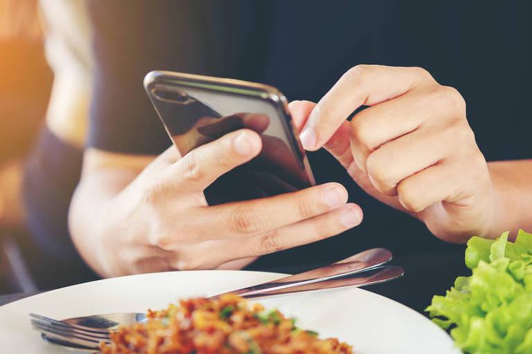 Homem segurando smartphone durante refeição