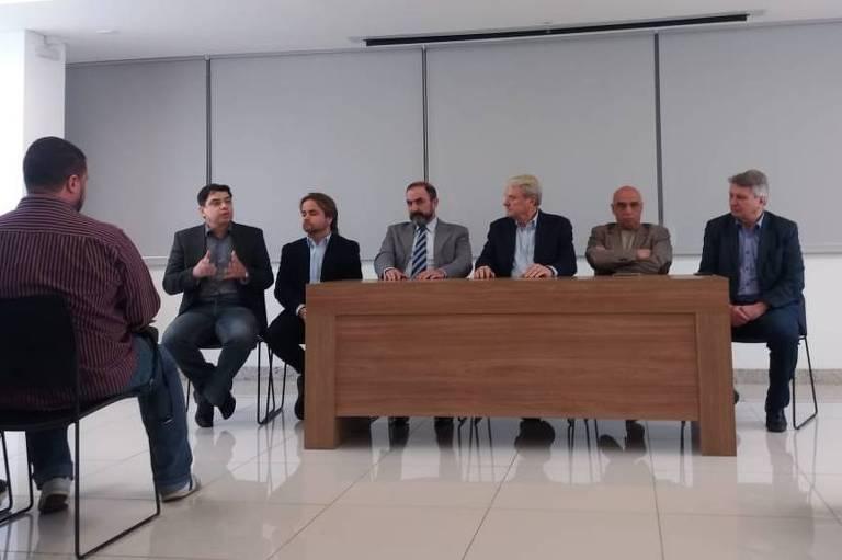 Representantes de partidos numa sala de reunião