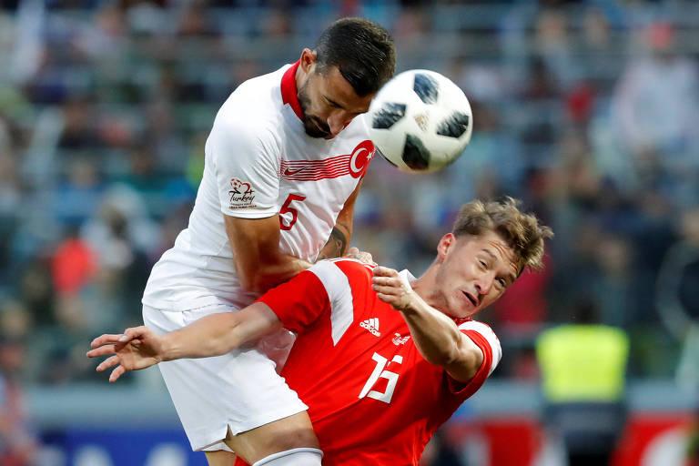 O turco Okay Yokuslu (à esq.) disputa bola com o russo Aleksei Miranchuk (à dir.) no amistoso, em Moscou