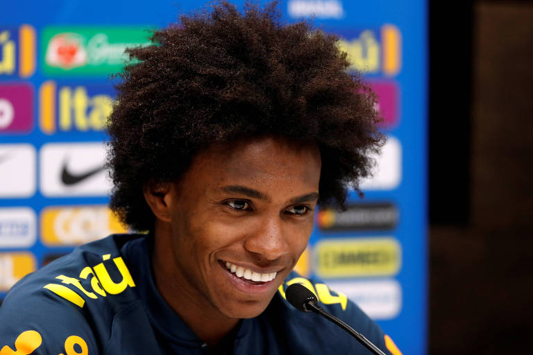 Atacante Willian sorrindo em entrevista coletiva no CT Tottenham
