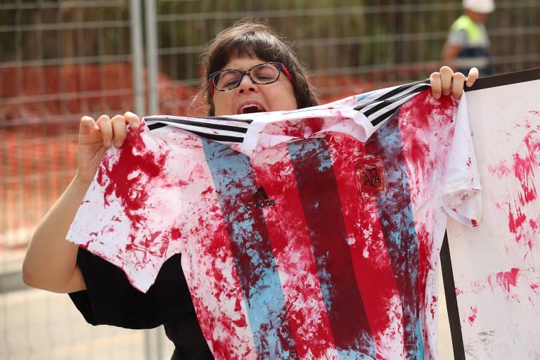 Manifestante pro-Palestina exibe camisa da Argentina pintada de vermelho, em protesto pelo amistoso contra Israel, que acabou cancelado nesta terça-feira