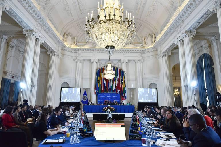 Chanceleres estão sentados em mesa azul, em um salão com arquitetura clássica e um lustre no meio. Atrás dos chanceleres estão os jornalistas.
