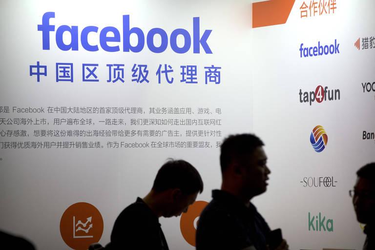 Visitantes à frente do logotipo do Facebook em feira de tecnologia em Pequim