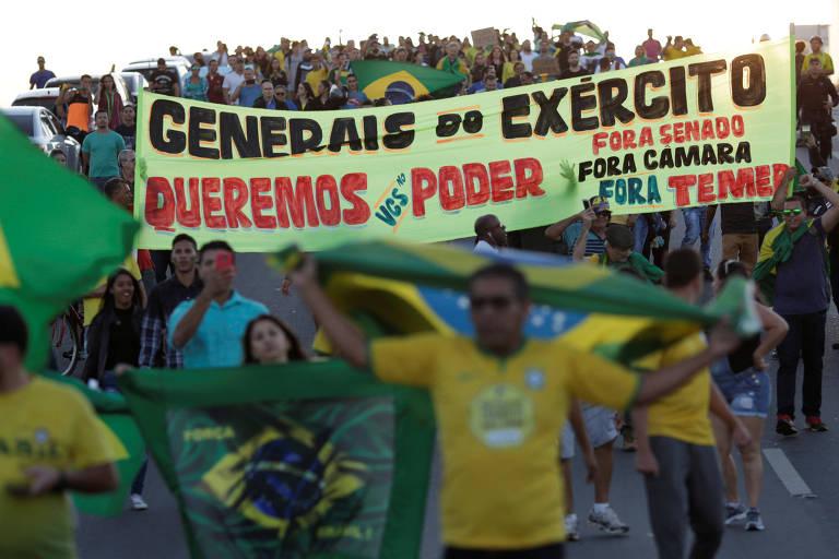 """Grupo com bandeiras do Brasil e vestindo camisetas verdes ou amarelas caminha por rua de Brasília. Uma das faixas traz a mensagem: """"Generais do Exército. Queremos o Poder. Fora, Senado. Fora, Câmara. Fora, Temer""""."""