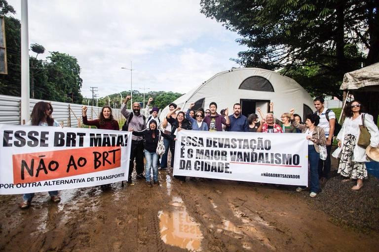 Ao lado de Guilherme Boulos, cerca de 30 manifestantes estendem faixa contra o BRT de Salvador