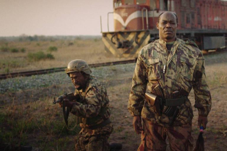 Cena do filme mostra um soldado de pé e outro agachado, com uma arma na mão