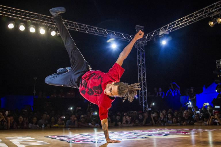 Homem equilibra o corpo em uma mão em movimento de break dance