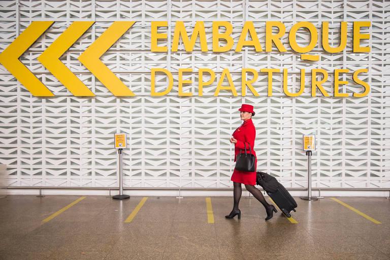 """Mulher de vermelho com chapéu puxa mala de carrinho preta, em frente a placa onde está escrito """"embarque"""""""