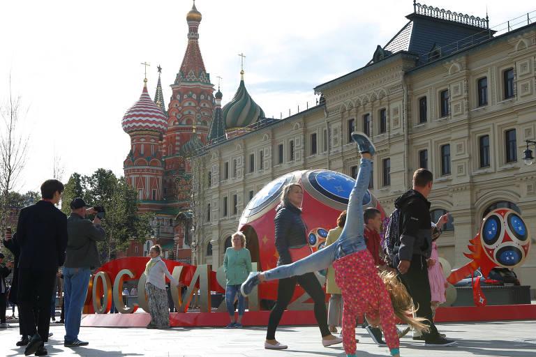 Menina brinca perto de escultura da Copa em Moscou