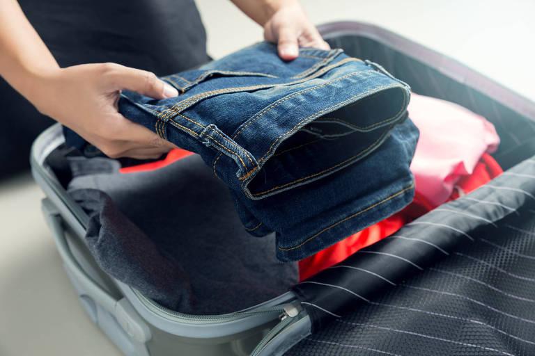 Pessoa colocando jeans dobrado em mala