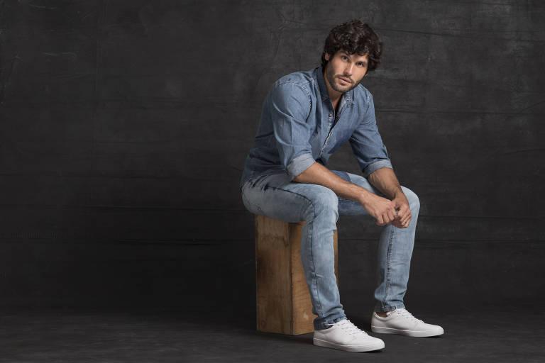 Ator Dudu Azevedo em foto posada, com roupa jeans, em cenário escuro